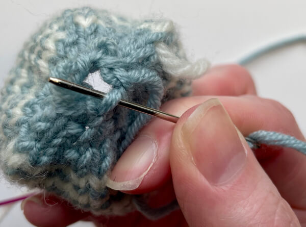 Close the base of the egg by gathering the cast on stitches