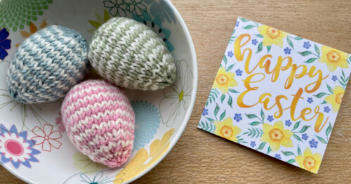 Striped knitted easter eggs in bowl with Easter card