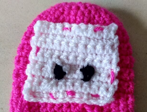 A few pink stitches to attach the white face to the head on the inside