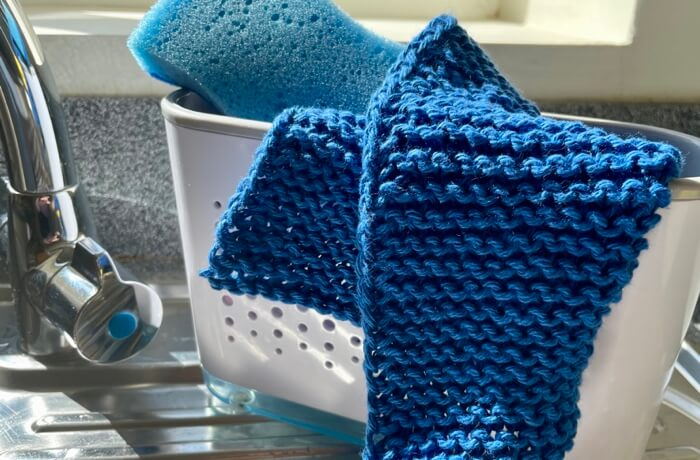 Close up of a square knitted cotton dishcloth beside sink