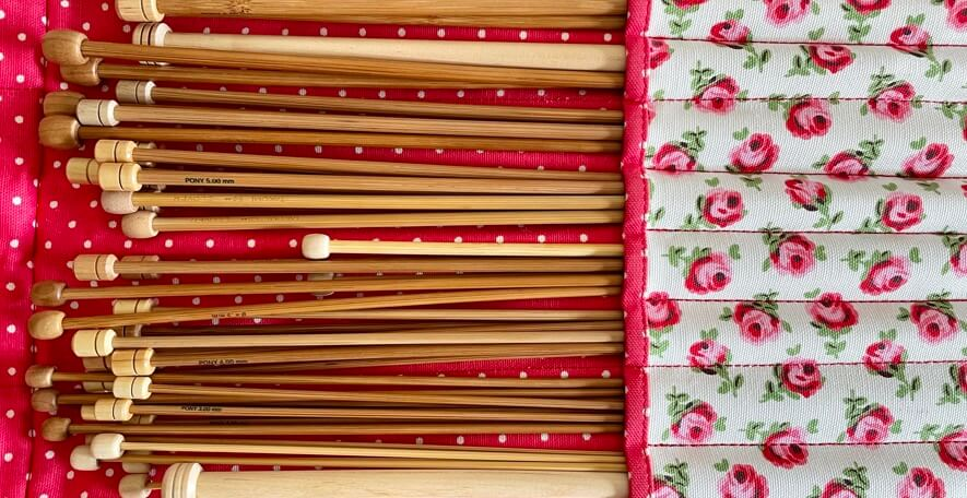 Assorted wooden and bamboo knitting needles in roll case