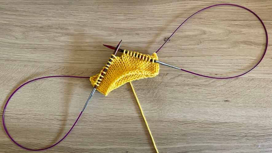 Magic loop knitting in progress with a long 'ear' of cable out each side